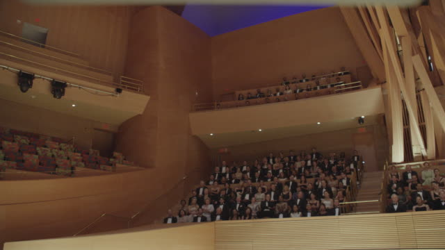 ms audience in formal attire seated in various sections of concert hall and applauding - concert hall stock videos & royalty-free footage