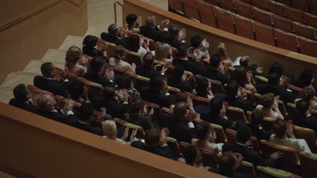 MS Audience in formal attire seated in various sections of concert hall and applauding