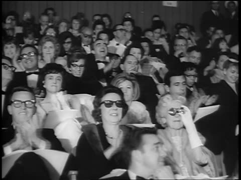 b/w 1964 audience in formalwear clapping at academy awards / newsreel - 1964 stock-videos und b-roll-filmmaterial