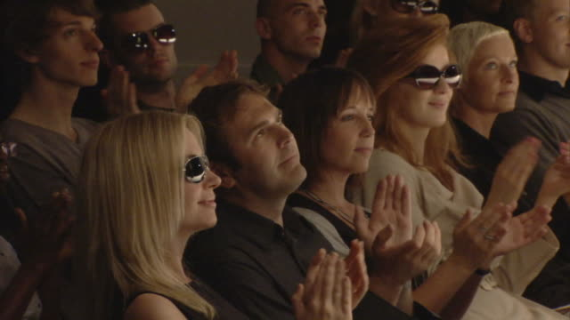 cu audience in front row applauding and looking up / london, england, uk - fascino video stock e b–roll
