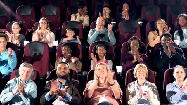 Audience in movie theater start clapping