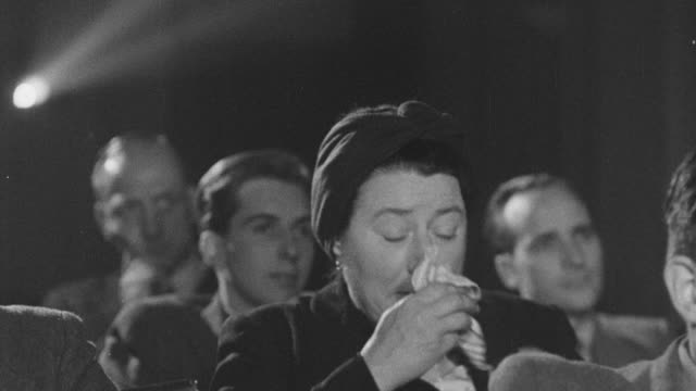 1947 ms audience member crying in movie theater / united kingdom - 映画館点の映像素材/bロール