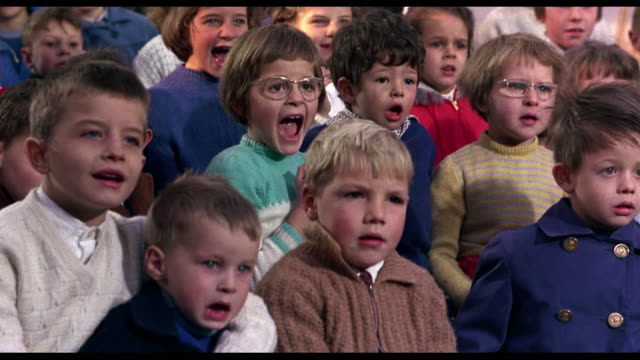 1963 audience of seated boys and girls laugh and scream - ridere video stock e b–roll