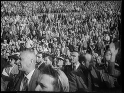 b/w 1951 audience outdoors at boxing match / some clapping cheering / berlin / newsreel - 1951年点の映像素材/bロール