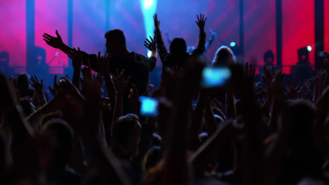 slo mo audience raising and waving hands at a concert - spettatore video stock e b–roll
