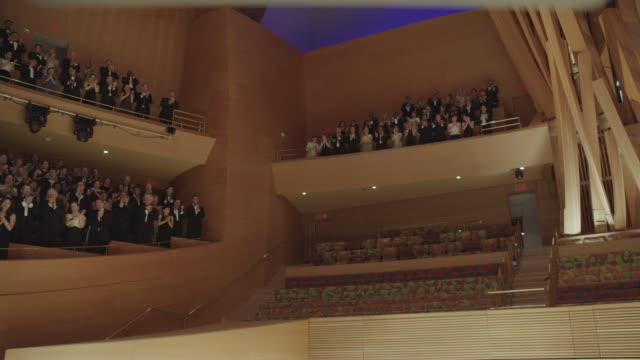 ms audience standing and applauding in formal attire in various sections of concert hall - concert hall stock videos and b-roll footage