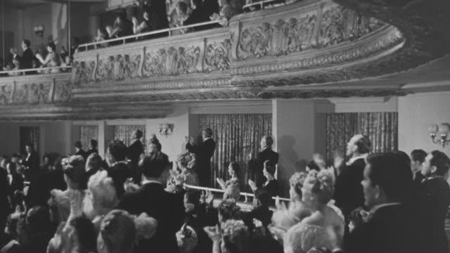 vídeos de stock e filmes b-roll de ms audience standing and clapping in section of theatre in formal attire - edifício de teatro
