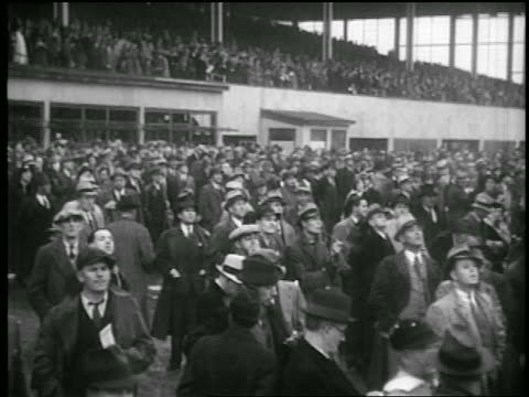 stockvideo's en b-roll-footage met b/w 1935 audience standing on ground and sitting in bleachers at horse race - 1935