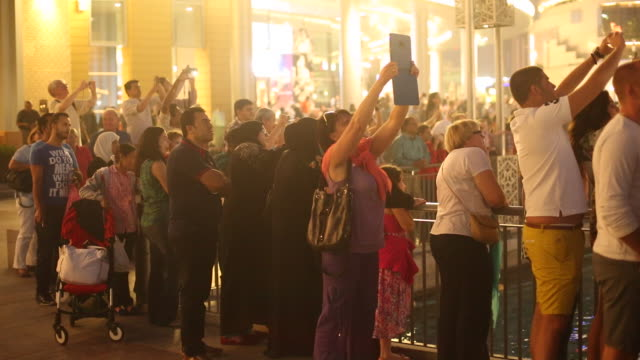 audience watches fountain show at dubai mall - tourist stock videos & royalty-free footage