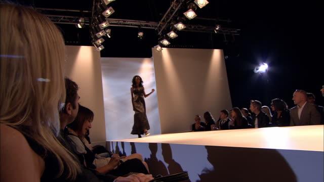 ws audience watching fashion show as model walks onto catwalk/ la ms pan model walking catwalk turning around, and walking back/ london, england - この撮影のクリップをもっと見る 1064点の映像素材/bロール
