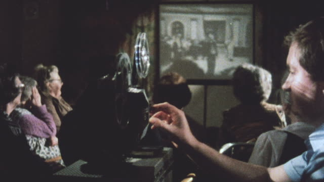 1983 MONTAGE Audience watching film being projected on wall, and operator adjusting projector / United Kingdom
