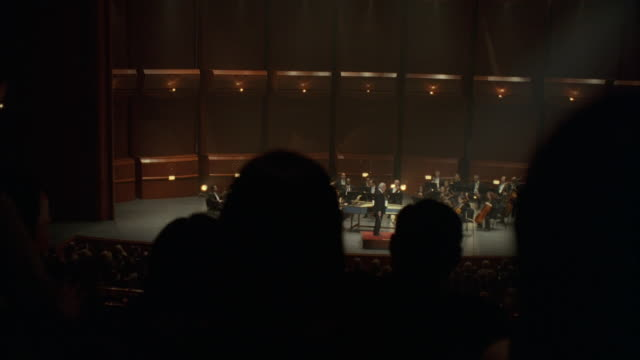 ms pan audience watching orchestra on stage in concert hall - orchestra stock videos & royalty-free footage