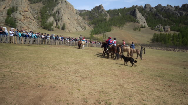 audience watching people horseback riding on landscape by rocky mountains - ulaanbaatar, mongolia - 遊牧民族点の映像素材/bロール