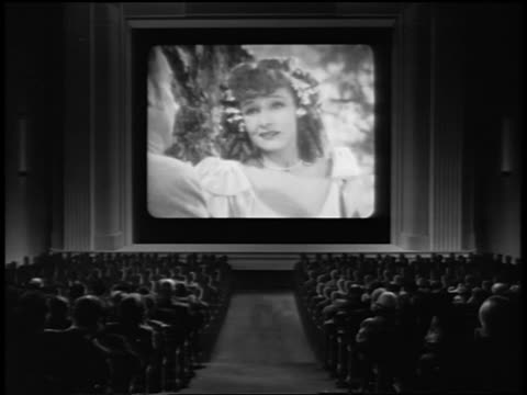 B/W REAR VIEW audience watching romantic musical on screen in movie theater / clapping