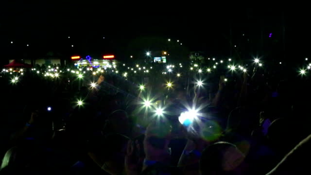vídeos de stock e filmes b-roll de audience with flashlights of smartphones in concert - evento de entretenimento