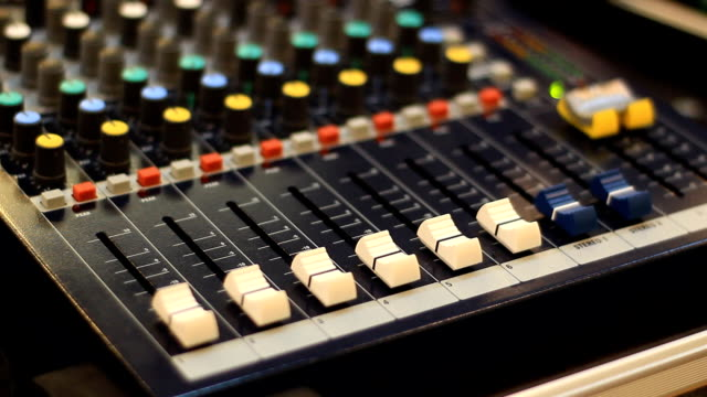 Audio Engineer adjusting faders on mixing console desk