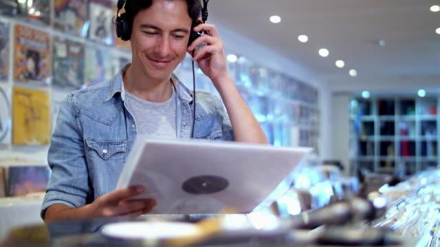 vídeos y material grabado en eventos de stock de 4k: hombre joven audiófilo en tienda de discos - tienda de discos