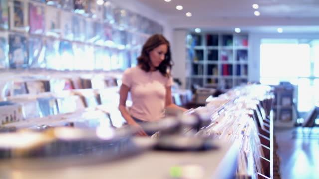 4 k: レコード店でオーディオファンの若い女性 - ミュージックショップ点の映像素材/bロール