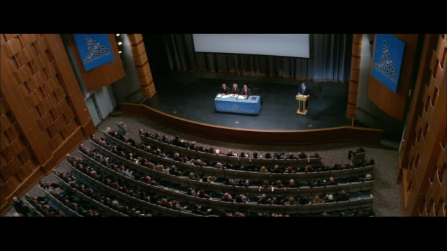 ha auditorium, with a panel on stage, moderator nearby, and audience listening - auditorium stock videos & royalty-free footage