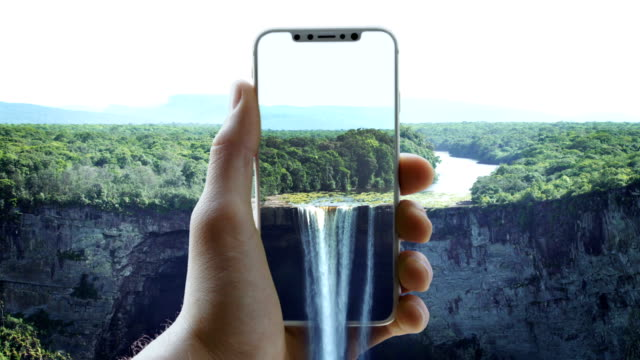 Augmented reality. Beautiful landscape locked in a smart phone. Waterfall pouring out of screen