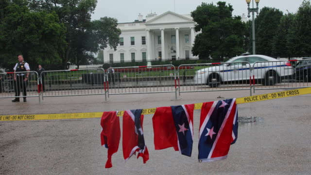 a torn up confederate flag is left on a police line near the white house by a protester after the unite the right 2 rally protesters in opposition to... - confederate flag stock videos & royalty-free footage