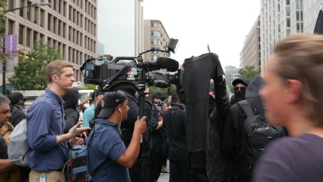 august 12 washington, d.c., usa: antifa blocks television reporters' video camera as protesters wait to block the exit of white nationalists being... - censorship stock videos & royalty-free footage