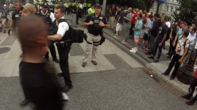 stockvideo's en b-roll-footage met protesters blocking the street are pushed away from the pennsylvania ave and 17th street nw by a member of the secret service after the unite the... - geheime dienstagent