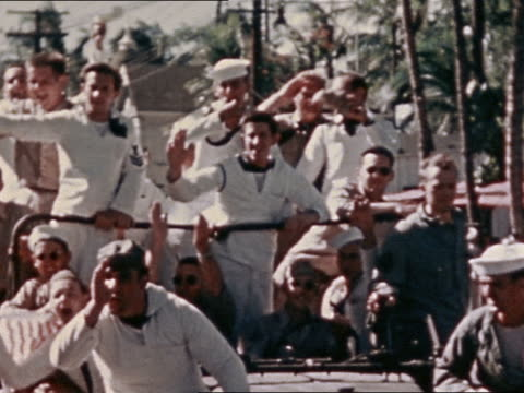 vidéos et rushes de august 14 1945 sailors waving from jeep driving down street in vj day parade / honolulu - 1945