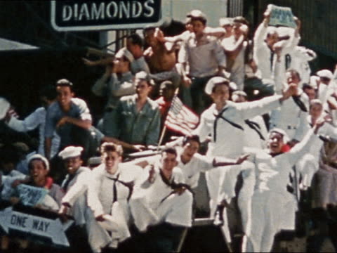 august 14, 1945 sailors waving us flags in vj day parade/ sailor holding newspaper with peace headline - allied forces stock videos & royalty-free footage