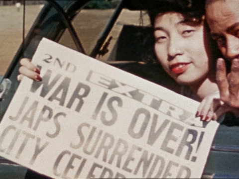 vídeos de stock, filmes e b-roll de august 14 1945 woman holding newspaper with headline 'war is over' and man flashing v sign / vj day - primeira página de jornal