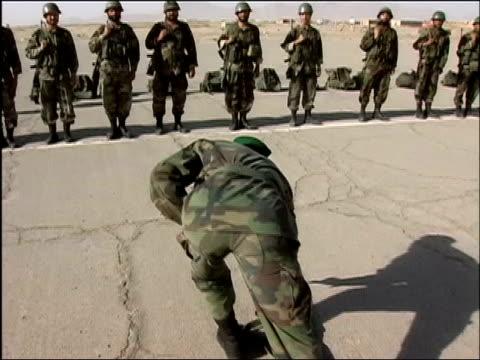 stockvideo's en b-roll-footage met august 14, 2004 wide shot afghan commander talking in front of troops/ tilt down commander bending down to pick up gun/ herat, afghanistan/ audio - bukken
