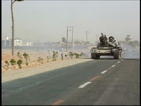 august 14, 2004 wide shot zoom in tank rolling down side of road with afghan militia forces loyal to ismail khan during interfactional fighting / herat, afghanistan/ audio - heckklappe teil eines fahrzeugs stock-videos und b-roll-filmmaterial