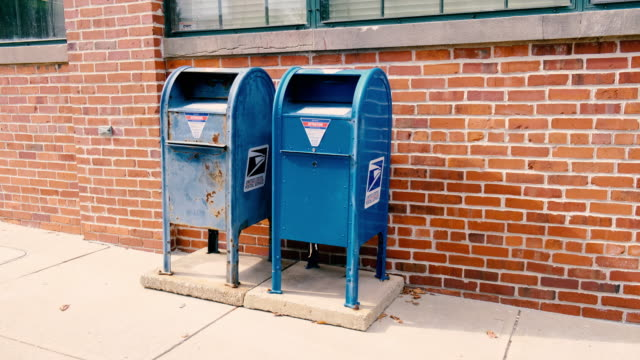 vídeos y material grabado en eventos de stock de august 14 bloomington, indiana, usa: a pair of blue united states post office mail collection boxes sit against a brick wall in the 300 block of w.... - usa