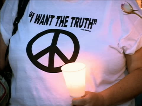 August 17 2005 Close up woman wearing 'I want the truth' peace sign Cindy Sheehan tshirt and holding a lantern at candlelight vigil at Camp Casey /...