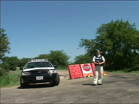 august 17, 2005 medium shot police man standing near car in front of blocked off road / crawford, texas - stop single word stock videos & royalty-free footage
