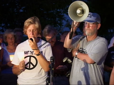 august 17, 2005 medium shot zoom in cindy sheehan wearing 'i want the truth' peace sign t-shirt while giving a speech at a candlight vigil at camp... - megaphone stock videos & royalty-free footage
