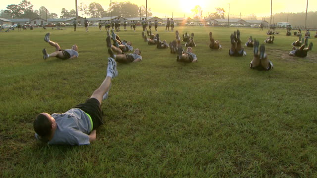 stockvideo's en b-roll-footage met august 19 2008 pan army soldiers doing early morning flutter kicks under sergeant's direction / fort stewart georgia united states - militaire training