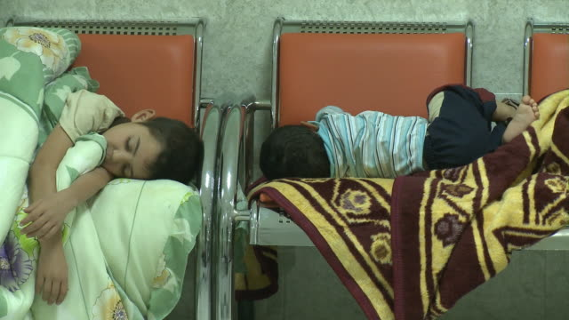 stockvideo's en b-roll-footage met august 19 2010 ms small children sleeping on chairs in triage of hospital / fallujah iraq - triage