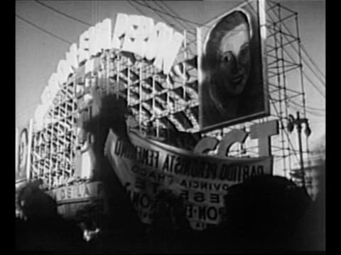 Huge crowd and marchers with banners at Buenos Aires rally in support of Juan and Eva Peron / large sign above platform Peron Eva Peron with photos...