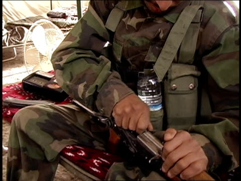 august 2004 closeup afghan national army soldier cleaning and assembling rifle in tent/ afghanistan - afghan national army stock videos & royalty-free footage