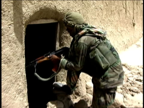 august 2004 closeup afghan national army soldier looking into entrance of building/ afghanistan - afghan national army stock videos & royalty-free footage