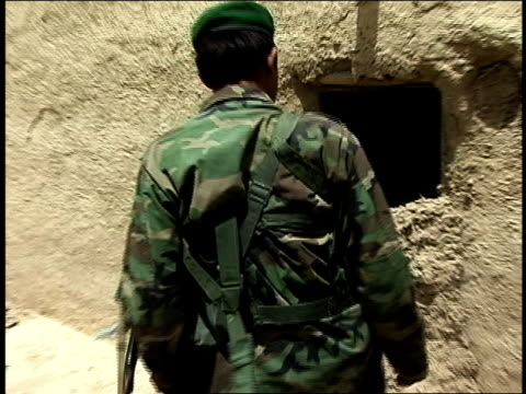 august 2004 closeup afghan national army soldiers digging cement out of doorway in building/ afghanistan - afghan national army stock videos & royalty-free footage