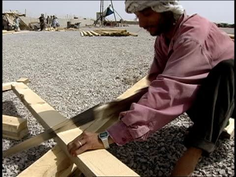 august 2004 medium shot afghan man working on construction site at afghan national army base/ kandahar afghanistan - afghan national army stock videos and b-roll footage
