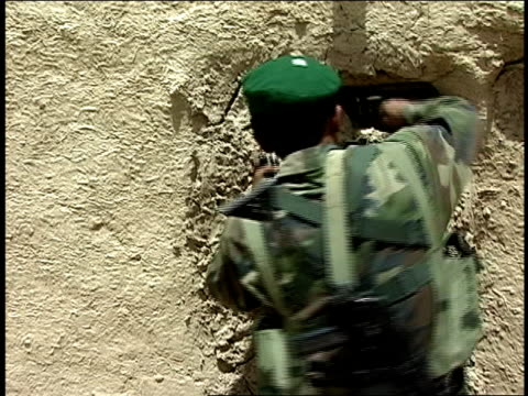 vídeos de stock e filmes b-roll de august 2004 medium shot afghan national army soldier digging cement out of doorway in building/ afghanistan - exército nacional afegão