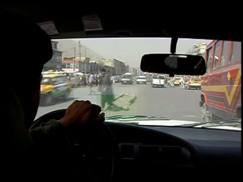 august 2004 medium shot afghan national army soldier driving army vehicle through traffic along crowded street/ afghanistan - personal land vehicle stock videos & royalty-free footage