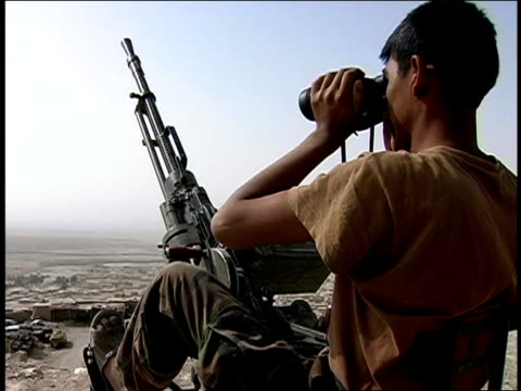 august 2004 medium shot afghan national army soldier looking through binoculars from hilltop/ afghanistan - operazione enduring freedom video stock e b–roll