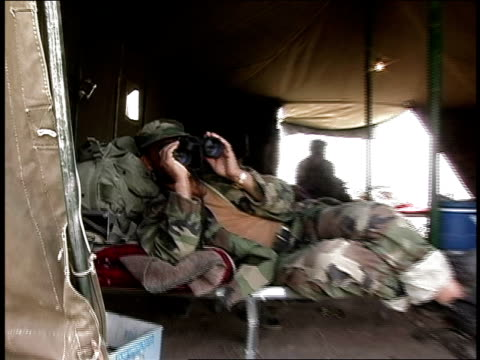 august 2004 medium shot afghan national army soldier looks through binoculars while lying on cot in tent/ afghanistan - afghan national army stock videos & royalty-free footage