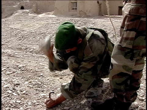 vídeos de stock e filmes b-roll de august 2004 medium shot afghan national army soldier pounding stake into ground with rock and another soldier pulling on rope/ afghanistan - exército nacional afegão