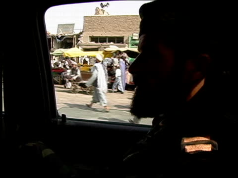 vidéos et rushes de august 2004 medium shot afghan national army soldier riding in army vehicle along crowded street/ afghanistan - moins de 10 secondes