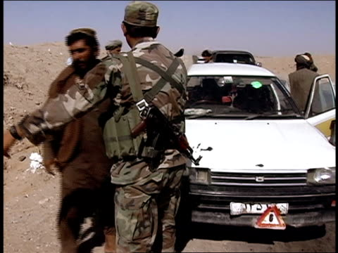 August 2004 Medium shot Afghan National Army soldier searching group of civilian men along road/ Afghanistan
